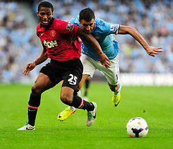 Manchester City's Aleksandar Kolarov jostles for the ball with Manchester United's Luis Antonio Valencia - Photo mandatory by-line: Dougie Allward/JMP - Tel: Mobile: 07966 386802 22/09/2013 - SPORT - FOOTBALL - City of Manchester Stadium - Manchester - Manchester City V Manchester United - Barclays Premier League
