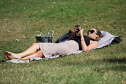 Image ©Licensed to i-Images Picture Agency. 16/07/2014. London, United Kingdom. Bright and hot day with max. temperatures of 27ºC. Woman lies in the grass in a sunny and hot day in central London. Hyde Park, London. Picture by Daniel Leal-Olivas / i-Images