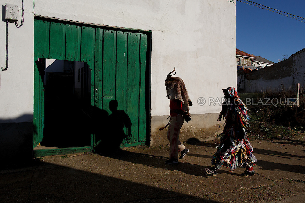 (L-R) Men dressed as La Filandorra and El Diablo prepare to enter a house during La Filandorra festival on December 26, 2016 in the small village Ferreras de Arriba, Zamora province, Spain.  La Filandorra festival is a pagan winter masquerade that takes place during Saint Esteban festivities. The parade is represented by four characters, La Filandorra, El Diablo (Devil), La Madama (madame) y El Galán (Gallant). (© Pablo Blazquez)