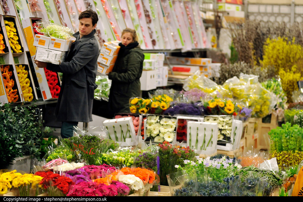 © Licensed to London News Pictures. 15/03/2012. London, UK. A couple buy flowers for their business. The Mothering Sunday sales rush is on for flower growers, suppliers, florists and retailers amongst the Flowers at the New Covent Garden Flower Market on March 15th 2012 in London, England. New Covent Garden Flower Market is London's premier wholesale market stocking the widest range of flowers, plants and foliage in the UK. The run up to Mothers' Day is crucial in the flower selling calendar as Mothers' Day sales are condensed into about four days making the market very busy. Traditionally, Mothering Sunday was a day when children, mainly daughters, who had gone to work as domestic servants, were given a day off to visit their mother and family. Today, Mother's Day is a time when children give flowers and cards to their mothers, and generally pamper them..  Photo credit : Stephen SImpson/LNP