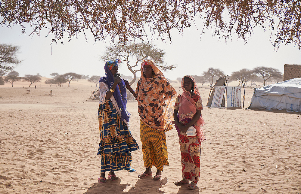 Women stand under a tree in the village of Guidan Kaji near the border with Nigeria on the outskirts of Diffa, Niger on February 13, 2016. Displaced people from Niger and Nigeria are sheltering in the village after fleeing at the nearby border. Many of the families had witnessed attacks by Boko Haram in their villages or had fled because of other villages around them being attacked. Caritas undertook a distribution of sleeping covers, mosquito nets, pots and money transfers.