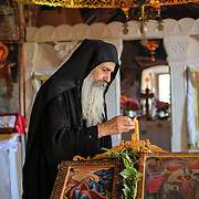 A Serbian Orthodox monk lights candles in preparation for the afternoon liturgy at Zavala Monastery, Zavala Village, Herzegovina.