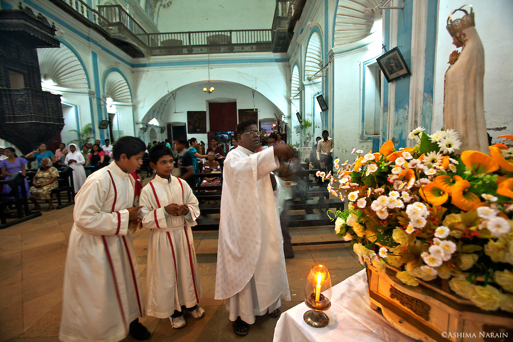 Our Lady of Fatima Procession is held every 13th May and 13th Otober in Diu, from St. Paul's Church. The 48 Catholic families of Diu honour the visions of three young children in Fatima, Portugal who saw the Virgin Mary on the 13th day of each month from May to October in 1917. <br /> Father Joseph Rodrigues brings the procession back to the church, and closes the ceremony.<br /> St. Paul's Church is dedicated to Our Lady of Immaculate Conception, and construction was completed in 1610. It's interiors are decorated with shell-like motifs, and it's wood carving is considered to be the finest of all the Portuguese Churches in India.