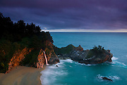 The 80-foot-tall McWay Falls, surging after several days of heavy rain, is colored by the setting sun as rain clouds continue to hang overhead. McWay Falls is one of the few waterfalls that empty directly into the Pacific Ocean. Such waterfalls are called tide falls. McWay Falls is located in the Big Sur region of California, south of Monterey.