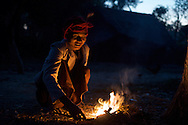 A woman warms herself by a fire early on a winter's morning, Mrauk U, Myanmar.