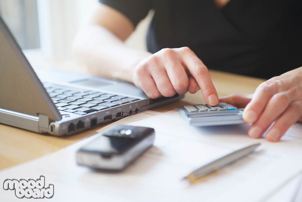 Man using calculator at desk with laptop cell phone and pen in foreground close-up mid section