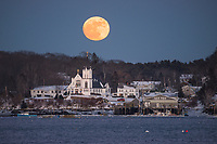 A full moon rises behind the iconic white church in Boothbay Harbor, Maine.