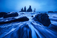 Rushing waves and moody blue hour light along the south coast of Iceland near Vik.