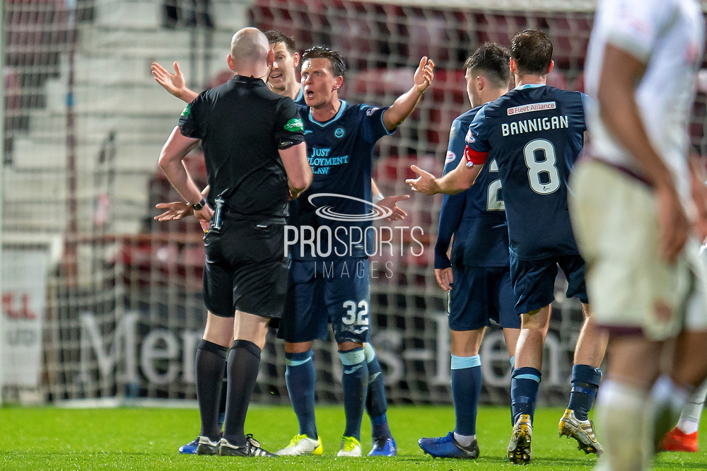Joe Cardle (#32) of Partick Thistle FC appeals to referee Bobby Madden for a penalty during the William Hill Scottish Cup quarter final replay match between Heart of Midlothian and Partick Thistle at Tynecastle Stadium, Gorgie, Edinburgh Scotland on 12 March 2019.
