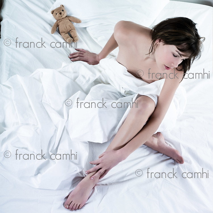 young beautiful woman in bed pensive