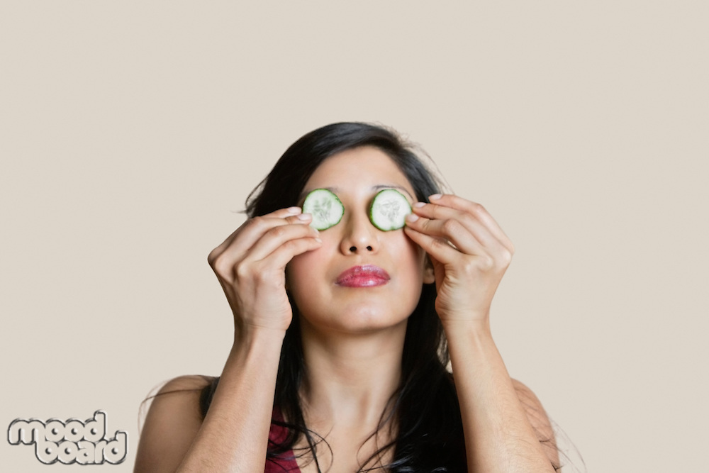 Young woman placing cucumber on eyes over colored background