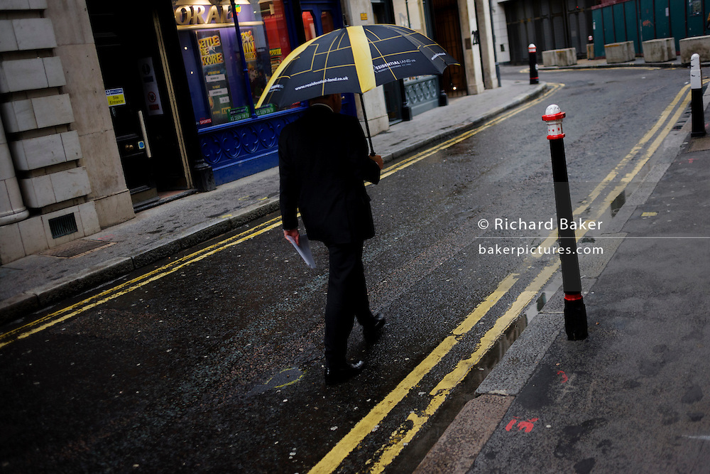 Businessman walks down quiet financial district back street carrying an umbrella whose stripes echo those of double-yellow lines