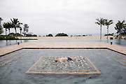 Ritz Carlton in Sanya, Yalong Bay. A man lies on water jets in the main pool.