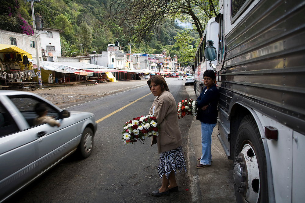 Women sell flower wreats on the road to Chalma. Chalma is the second most important pilgrimage site in Mexico.  People come from all over the country to visit the Senor de Chalma. They often arrive wearing crowns made of flowers, and leave the crowns at the church.
