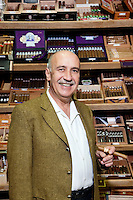 Portrait of a male owner of tobacco shop standing with cigar boxes in background