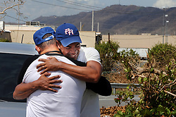 Carlos Rolâ¤â€n (right), a financial planner from the town of San Lorenzo, stops along the Caguas road to meet and say good bye to a coworker after his decision to leave Puerto Rico with his family on October 2. It is a decision against their will since their house got damaged, he is jobless and their daughters' schools are closed for an unknown amount of time forcing many Puerto Ricans to fly to the U.S. after Hurricane Maria, (category 4) passed through Puerto Rico devastating the island leaving residents without power and ways to communicate on Sept. 20. on October 02, 2017. Photo by Pedro Portal/Miami Herald/TNS/ABACAPRESS.COM