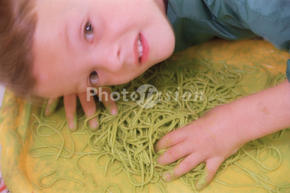 Nursery school child playing with coloured spaghetti,