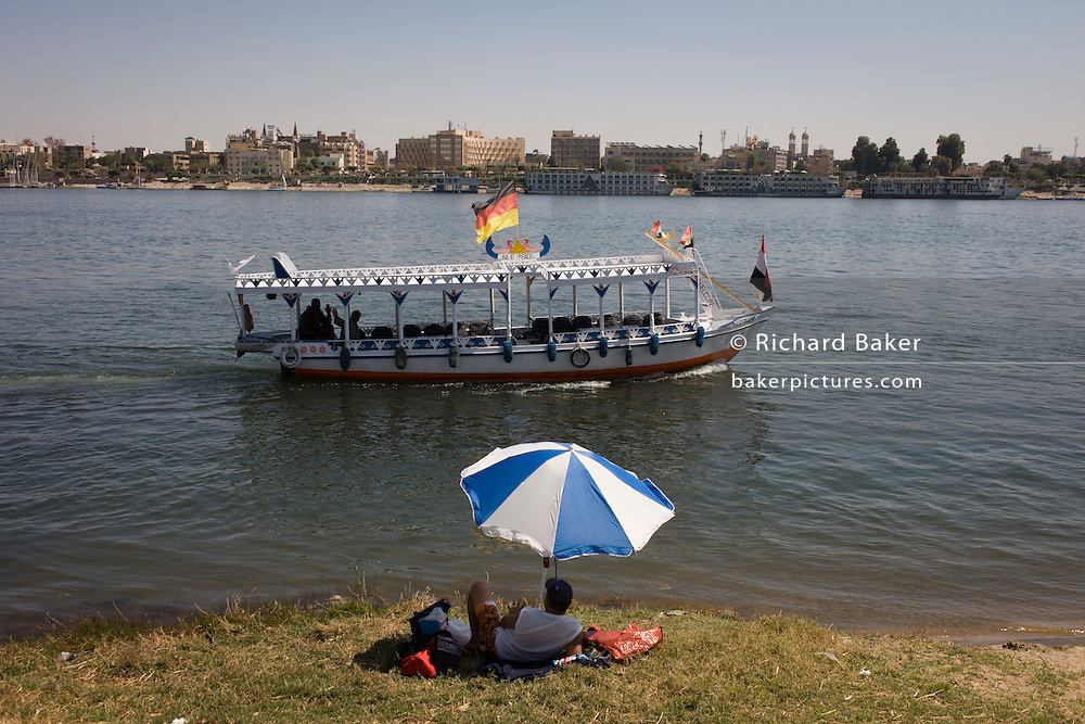 A privately-owned motorboat ferry flying the German flag and dependent on all tourist trade crosses the River Nile in front of a sunbather at Luxor, Nile Valley, Egypt.