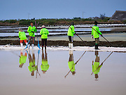 09 MARCH 2015 - NA KHOK, SAMUT SAKHON, THAILAND: Workers on a salt farm walk through a salt pond. The coastal provinces of Samut Sakhon and Samut Songkhram, about 60 miles from Bangkok, are the center of Thailand's sea salt industry. Salt farmers harvest salt from the waters of the Gulf of Siam by flooding fields and then letting them dry through evaporation, leaving a crust of salt behind. Salt is harvested through dry season, usually February to April. The 2014 salt harvest went well into May because the dry season lasted longer than normal. Last year's harvest resulted in a surplus of salt, driving prices down. Some warehouses are still storing salt from last year. It's been very dry so far this year and the 2015 harvest is running ahead of last year's bumper crop. One salt farmer said prices are down about 15 percent from last year.    PHOTO BY JACK KURTZ