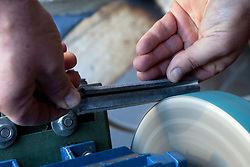 """Avigliano (PZ), 04-10-2010 ITALY - Vito Aquila, artigiano di Balestre. Il coltello di Avigliano, comunemente conosciuto come """"balestra"""", impreziosito con decorazioni in argento e ottone che le conferivano un certo valore non solo artistico,ha identificato per tutto l'Ottocento e parte del Novecento il carattere fiero e risoluto del popolo aviglianese, come attestato in una lunga casistica di riscontri documentari. La """"balestra"""" è un'arma a tutti gli effetti, ed è già considerata -nell'ambito delle manifatture di ferro - oggetto di pregio. Per l'approvvigionamento dell'argento e dell'ottone destinati alla decorazione del manico del coltello gli armieri si rivolgevano agli orefici o agli ottonari. La """"balestra"""" era un'arma del popolo, pronta ad essere impiegata, a seconda delle circostanze, per la difesa o l'offesa tanto dagli uomini quanto dalle donne. Queste, la ricevevano come regalo di fidanzamento dal rispettivo promesso sposo per meglio difendere il proprio onore, perpetrando un'usanza molto sentita almeno fino ai primi decenni del '900..Nella Foto: La lavorazione del manico in corno di bufalo."""