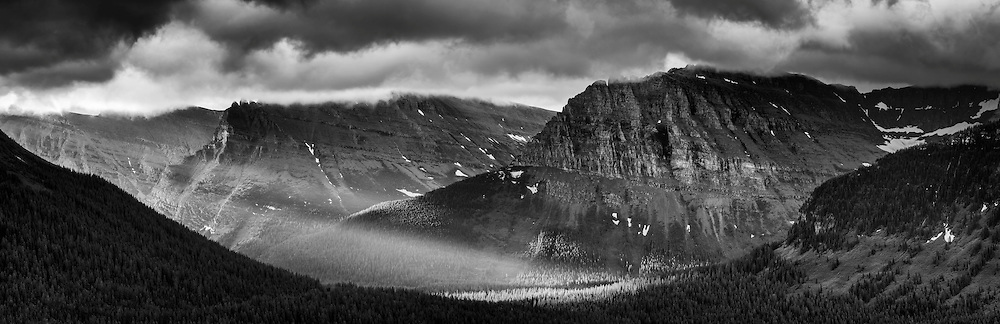 The rising sun breaks through thinning storm clouds near the top of the Going to the Sun road, in the Logan Pass region of Glacier National Park, Montana, USA