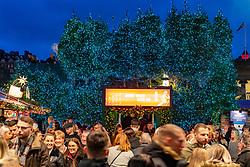 Crowds of people outside Johnnie Walker Bothy Bar in Edinburgh Christmas Market in West Princes Street gardens in Edinburgh, Scotland, UK
