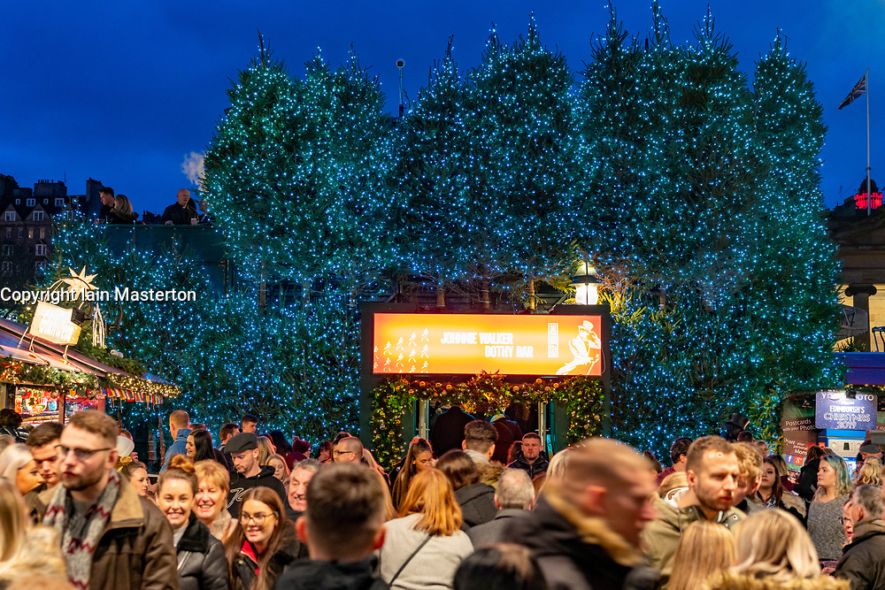 Crowds of people outside Johnnie Walker Bothy Bar in Edinburgh Christmas Market in West Princes Street gardens in Edinburgh, Scotland, UK