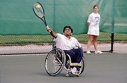 Young man with disability; who is wheelchair user; playing game of tennis,