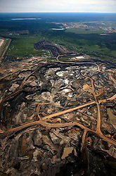 CANADA ALBERTA FORT MCMURRAY 20JUL09 - Aerial view of Shell Albian Sands tarsands mine and tailings pond in the Boreal forest north of Fort McMurray, northern Alberta, Canada...The tar sand deposits lie under 141,000 square kilometres of sparsely populated boreal forest and muskeg and contain about 1.7 trillion barrels of bitumen in-place, comparable in magnitude to the world's total proven reserves of conventional petroleum. Current projections state that production will  grow from 1.2 million barrels per day (190,000 m³/d) in 2008 to 3.3 million barrels per day (520,000 m³/d) in 2020 which would place Canada among the four or five largest oil-producing countries in the world...The industry has brought wealth and an economic boom to the region but also created an environmental disaster downstream from the Athabasca river, polluting the lakes where water and fish are contaminated. The native Indian tribes of the Mikisew, Cree, Dene and other smaller First Nations are seeing their natural habitat destroyed and are largely powerless to stop or slow down the rapid expansion of the oil sands development, Canada's number one economic driver...jre/Photo by Jiri Rezac / GREENPEACE..© Jiri Rezac 2009
