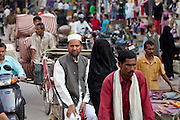 Muslim couple in crowded street scene during holy Festival of Shivaratri in city of Varanasi, Benares, Northern India