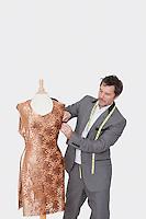 Mature male fashion designer adjusting cloth on tailor's dummy over gray background