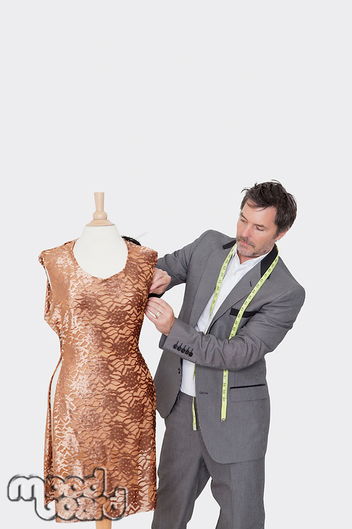 Mature male fashion designer adjusting cloth on tailor's dummy over gray background