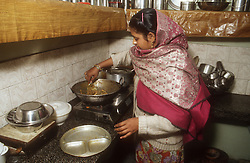Kitchen of middleclass family in Gobindigarh; Punjab; India; with mother cooking on small gas cooker,