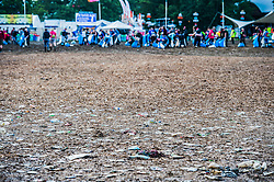 The rubbish is trampled into the mud but an army of voulunteers has already cleared a large area (leaving a clear line) in the now empty Other Stage crowd area - the festival motto is 'Leave no trace'.The 2015 Glastonbury Festival, Worthy Farm, Glastonbury.