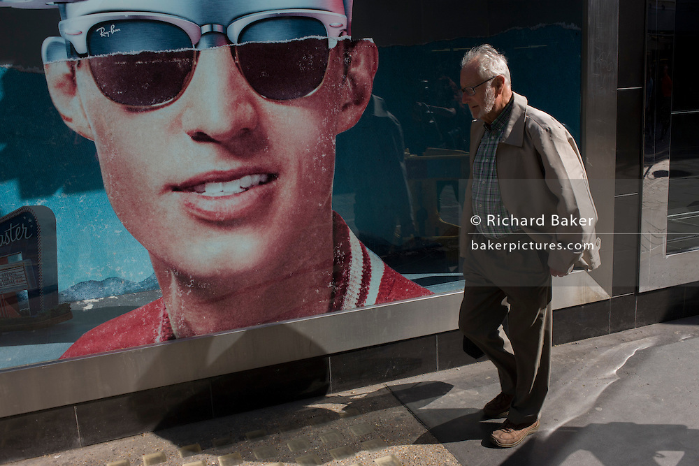 An elderly gentleman passes-by a poster of a model wearing stylish shades outside a sunglasses shop window selling Ray Bans on Long Acre in London's Covent Garden.