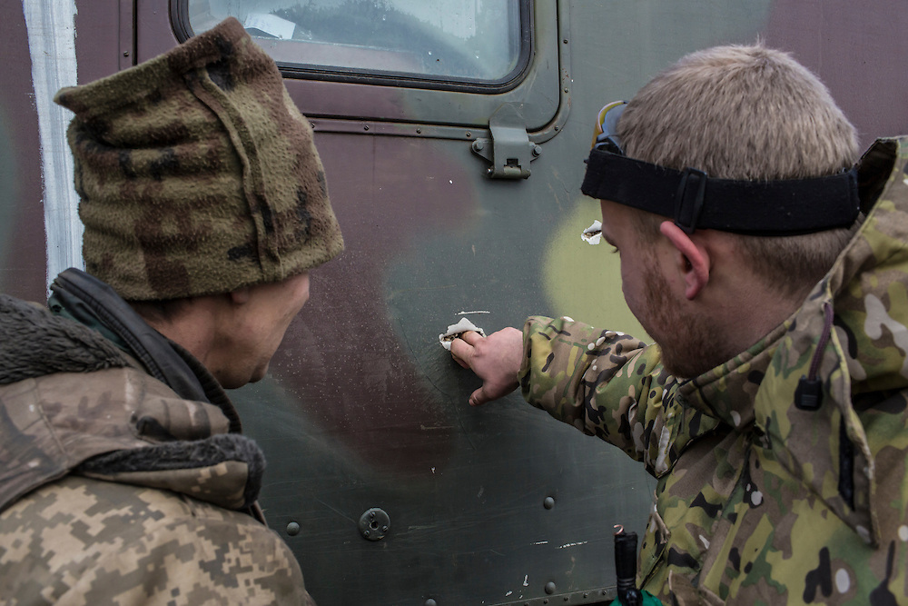 ARTEMIVSK, UKRAINE - FEBRUARY 19: Ukrainian soldiers from a unit based in Zaporizhia examine bullet holes in their truck received during their withdrawal from Debaltseve the previous day on February 19, 2015 in Artemivsk, Ukraine. Ukrainian forces started withdrawing from the strategic and hard-fought town of Debaltseve yesterday being effectively surrounded by pro-Russian rebels. (Photo by Brendan Hoffman/Getty Images) *** Local Caption ***