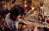 Leather artist Seken Nurgaliyev learnedd his craft from his father, Zhumagazy (at center rear), a master leather craftsman in the village of Shiber-Aul.  A territorial governor, whose prized falcon had lost part of its talon, asked Zhumagazy to help restore it with his leather craft.  His work was so successful that the governor offered him his daughter's hand in marriage.  Zhumagazy accepted.  In this photo, Seken is working on a representation of Zhambil, the master of improvised poetry (1846-1945), whose themes were struggles between good and evil, and compassion for people' misfortunes.