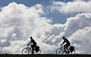 Only as silhouette, two cyclists are to be recognized on the or dike in the Brandenburg, Germany. ride wine (MŠrkisch or country) on Thursday (17.07.2008). Photo:  Patrick Pleul +++(c) dpa - report + + +