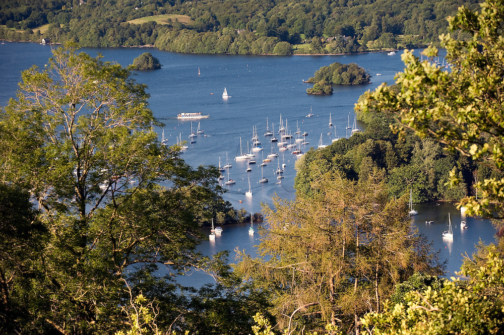 Lake District National Park, Cumbria, England. Boat moorings off Belle Isle in Windermere seen from woodland path below Claife