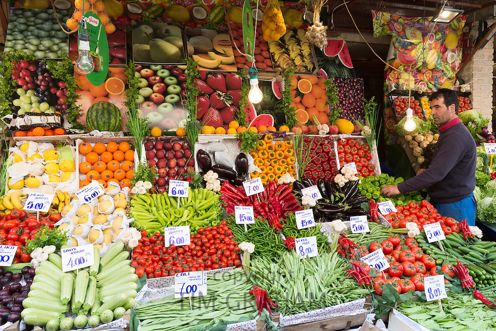 Shopkeeper with fresh fruit and vegetables with Turkish lira prices at food market Kadikoy Asian Istanbul Turkey