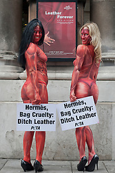 "© licensed to London News Pictures. London, UK 08/05/2012. Three models representing PETA, painted to resemble skinned and bloodied people, holding signs reading ""Hermès, Bag Cruelty: Ditch Leather"" and posing to protest against the leather industry, outside the opening of the ""Hermès Leather Forever"" exhibition at the Royal Academy of Arts today (08/05/12) Model names: (left to right) Maria Harris and Katy Heffernan Smith. Photo credit: Tolga Akmen/LNP"
