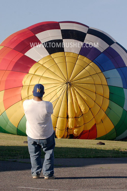 A worker holds down a balloon with rope as the balloon is filled with hot air at Randall Airport in Middletown, N.Y. July 2, 2005.