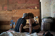 "In this Sept. 11, 2017 photo, Jayanne Pessanha, left, and Yara Andrade, kiss in their room in a squatter building that used to house the Brazilian Institute of Geography and Statistics (IBGE) in the Mangueira slum of Rio de Janeiro, Brazil. ""Those who are here have faith. They have faith that they will leave this place,"" said Pessanha. (AP Photo/Felipe Dana)"