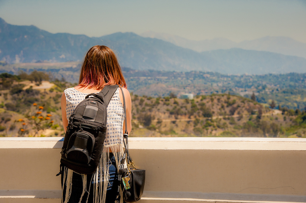 The back of a young woman looking at a scenic view of the mountains at the Griffith Observatory in Los Angeles, California