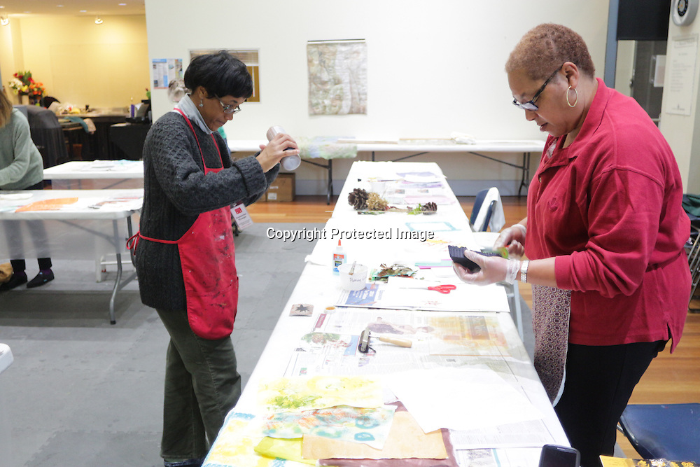 """Instructor September Krueger, left, mixes paint while Althea Johnson paints a quilt square during """"Create Your Own Quilt Squares"""" Sunday November 23, 2014 at the Cameron Art Museum in Wilmington, N.C. (Jason A. Frizzelle)"""