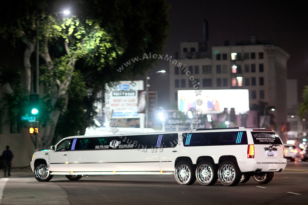 A strangely long car, resembling a mix between a limousine and an SUV, is running along the streets of central Los Angeles, California, USA.