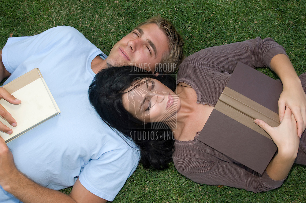 Attractive, young couple lying in the grass with books