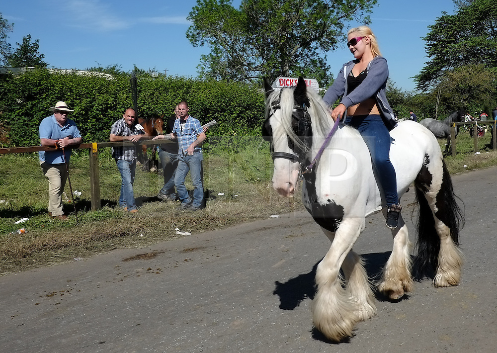 © Licensed to London News Pictures. <br /> 06/06/2014. <br /> <br /> Appleby, Cumbria, England<br /> <br /> A girl rides her horse along the road as gypsies and travellers gather during the annual horse fair on 6 June, 2014 in Appleby, Cumbria. The event remains one of the largest and oldest events in Europe and gives the opportunity for travelling communities to meet friends, celebrate their music, folklore and to buy and sell horses.<br /> <br /> The event has existed under the protection of a charter granted by King James II in 1685 and it remains the most important event in the gypsy and traveller calendar.<br /> <br /> Photo credit : Ian Forsyth/LNP
