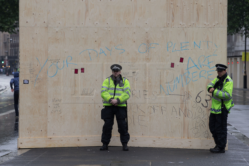 © Licensed to London News Pictures . 20/06/2015 . London , UK . Police alongside the Women of War memorial on Whitehall , which is protected by graffitied wood boards . Tens of thousands of people march from the Bank of England to Parliament , to protest economic austerity in Britain . Photo credit: Joel Goodman/LNP