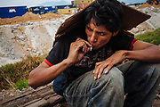 "A Honduran immigrant smokes a cigarette and cover himself from the raining with a piece of cardboard while waits beside of the railroad to climb ""the beast"" or ""train of death"", referring to the freight train where thousands of migrants travel with the intention of reaching to United States, in State of Mexico, Mexico, August 20, 2008."